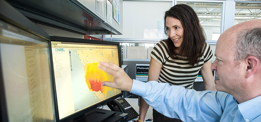 Photo of Suzanne Tegen of the Market and Policy Impact Analysis group at NREL's Strategic Energy Analysis Center and Nate Blair, Manager of the Energy Forecasting and Modeling group, looking at a computer screen showing a renewable energy risk performance model.