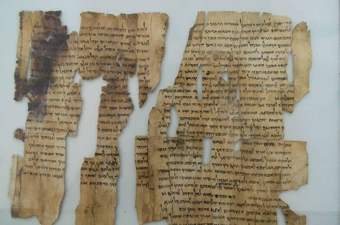 An image shows a few fragmented pieces of the famous Dead Sea Scrolls, showing black ink scrawled on tattered parchment.