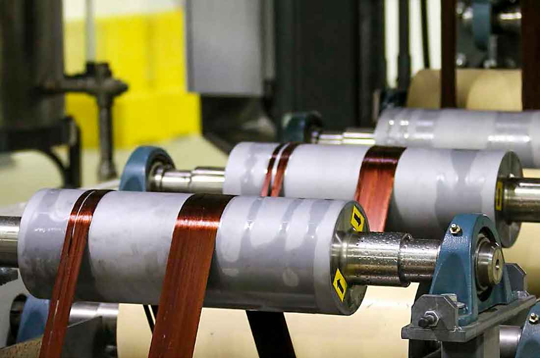 An image displays threads of carbon fiber on a manufacturing line.